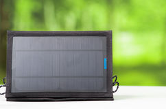 Portable black solar charger sitting on white surface, modern green technology concept, garden window background.  Royalty Free Stock Images