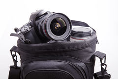 Portable camera bag. Close-up of portable camera bag with dslr camera and lens on white Royalty Free Stock Photography