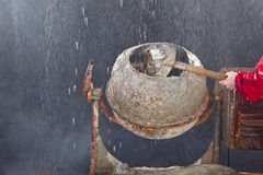 Worker putting sand in cement mixer Royalty Free Stock Photography