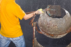Worker putting sand in cement mixer Royalty Free Stock Photos