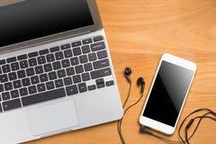 Portable computer laptop, smartphone, earphones, pencil, paper Stock Photos