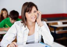 Portable de réponse d'adolescente dans la salle de classe Photographie stock libre de droits