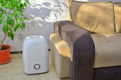 Portable dehumidifier collect water. From air inside of living room royalty free stock photography