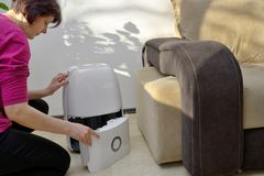 Portable dehumidifier collect water from air. Inside of living room stock images