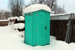 Portable ecological toilet on construction site during winter. Portable ecological toilet covered and surrounded with freshly fallen snow, wire fence and royalty free stock images
