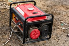 Portable elctric generator working on petrol close. Close up small red electric generator on ground royalty free stock images