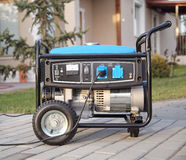 Portable electric generator. Gasoline powered portable generator at home Stock Photos