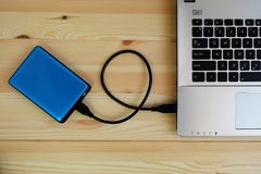 Portable external hard drive USB3.0 connect to laptop computer on wooden. Background royalty free stock image