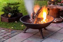 A portable fireplace with bright burning firewood making sparks and smoke at the backyard or garden near house. A place for eveni. Ng meeting and stories royalty free stock images