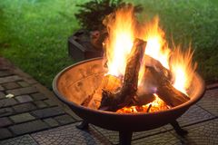 A portable fireplace with bright burning firewoods making sparks. And smoke at the backyard or garden near house. A place for evening meeting and stories royalty free stock image
