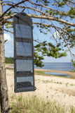 Portable foldable solar panel battery hanging on the outdoors on a pine tree Stock Photos