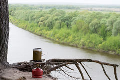 Portable gas burner stay in sand over a cliff above the river Stock Photography