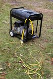 Portable Generator. Portable electric generator with power cords attached sits on grass Royalty Free Stock Image