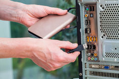 Portable hard drive. Men plug in a portable hard drive Royalty Free Stock Images