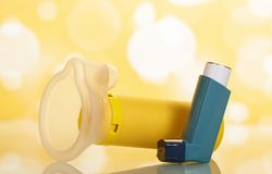 Portable inhaler and children`s mask for asthmatics, on yellow Royalty Free Stock Image