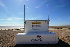 Lifeguard cabin on a deserted beach. A portable lifeguard cabin seen on a southern UK beach late in the afternoon.  The empty beach is pebbled and the tide has Stock Photography