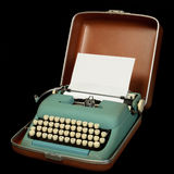 Portable manual typewriter. Vintage portable typewriter with 1960s colors in carrying case; isolated on black Stock Photo