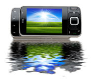 Portable modern mobile phone with a nice greenfiel. D with water reflection Stock Photo