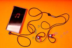 Portable music player on orange background with earphones and wire stock images