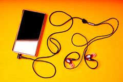 Portable music player on orange background with earphones and wire royalty free stock photos
