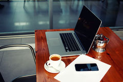 Portable net-book with cell telephone lying on a wooden table in coffee shop interior, freelance distance work, filtered image Stock Photo