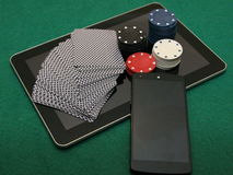Portable online casino. 21st century casino - online casino. Deck of cards, chip, and mobile phone on the tablet stock photos