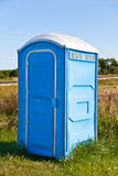 Portable Out House. A blue portable toilet in the grass stock images