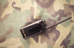 Portable radio on a fabric with camouflage pattern. Toned Stock Photo
