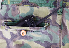 Portable radio in a pocket of pants with camouflage pattern Stock Image