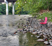 Portable Red Folding Chair on the Banks of the Lehigh River, USA Royalty Free Stock Image