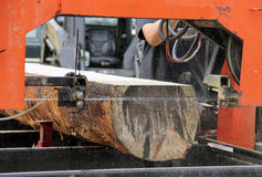 Portable saw mill. Cutting a log into lumber with saw dust in the air from the cutting Royalty Free Stock Images