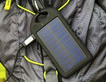 Portable solar cell hanging on tourist backpack. Closeup Stock Photos