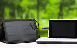 Portable solar charger sitting on white desk surface connected to tablet, modern technology concept, window garden Royalty Free Stock Photo
