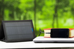 Portable solar charger sitting on white desk surface connected to tablet, modern technology concept, window garden Stock Images