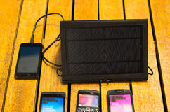 Portable solar charger sitting on wooden surface next to four mobile phones, as seen from above, modern green technology Royalty Free Stock Image