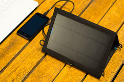 Portable solar charger sitting on wooden surface next to laptop computer and mobile phone, as seen from above, modern Stock Image