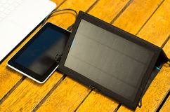 Portable solar charger sitting on wooden surface next to laptop computer and tablet, as seen from above, modern. Technology concept Royalty Free Stock Photography