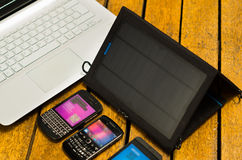 Portable solar charger sitting on wooden surface next to laptop computer and three smartphones, as seen from above. Modern technology concept Stock Photo