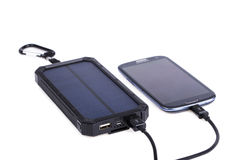 Portable solar charger for smart phone. Royalty Free Stock Photo