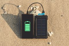 Portable solar panel is on the beach. In the sand and charges the battery of the frameless mobile phone. use of solar energy in the wild on a desert island Stock Photos