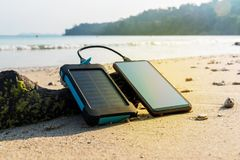Portable solar panel is on the beach. In the sand and charges the battery of the mobile phone. use of solar energy in the wild on a desert island. Modern Stock Photos