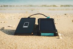 Portable solar panel is on the beach. In the sand and charges the battery of the mobile phone. use of solar energy in the wild on a desert island Royalty Free Stock Images
