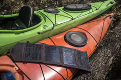 Portable solar panels lie on a kayak and accumulate energy. Stock Images