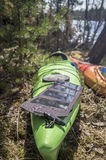 Portable solar panels lie on a kayak in the forest and accumulat Stock Photos