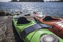 Portable solar panels lie on a kayak by the lake and accumulate Stock Images