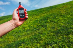 Portable thermometer in hand measuring outdoor air temperature and humidity Stock Images
