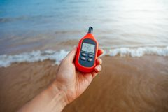 Portable thermometer in hand measuring outdoor air temperature and humidity. Closeup view Royalty Free Stock Photography