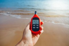 Portable thermometer in hand measuring outdoor air temperature and humidity. Closeup view Royalty Free Stock Image