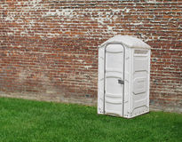 Portable Toilet By Brick Wall. Royalty Free Stock Image