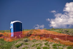 Portable toilet and orange fence Stock Images